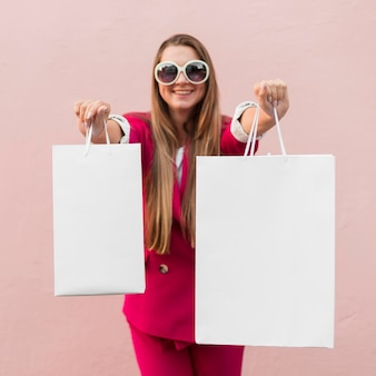 Cliente vistiendo ropa de moda mostrando bolsas de la compra.