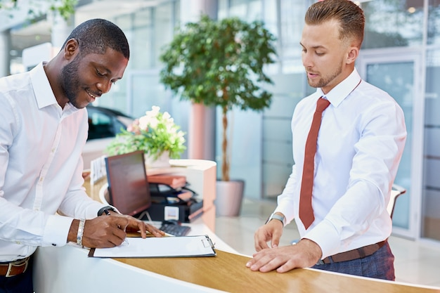 Clientes africanos firmando papeles con el vendedor en la tienda del concesionario