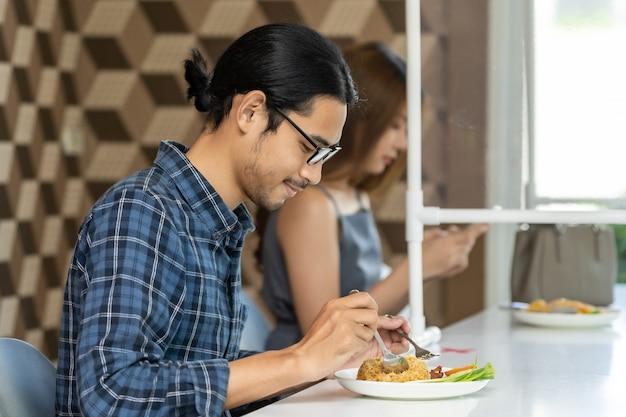 Clientes asiáticos comiendo en un nuevo café normal con distancia social