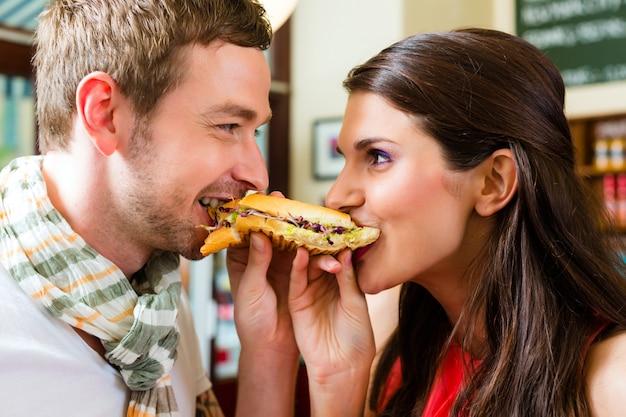 Clientes que comen hot dog en un bar de comida rápida