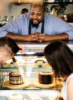 Clientes que eligen pastel en la nevera de exhibición