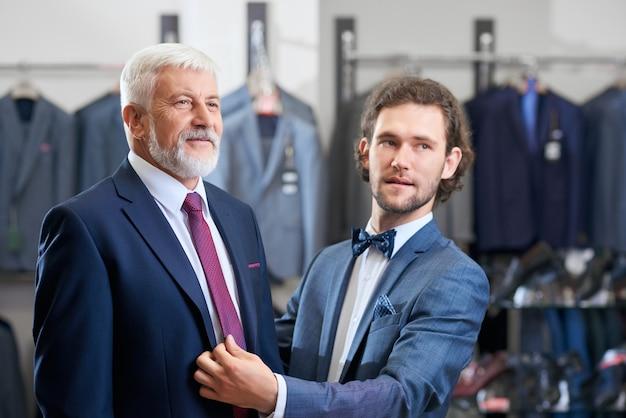 Clientes que eligen trajes de moda en la tienda.