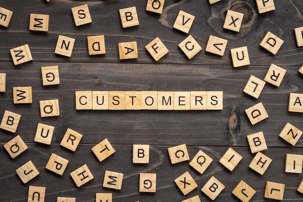 Los clientes redactan el bloque de madera en la tabla para el concepto del negocio.