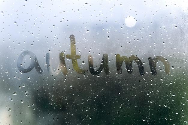 Clima lluvioso, la inscripción otoño en el cristal sudoroso