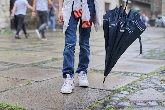 Clima lluvioso, piernas de niña con paraguas