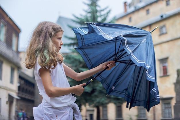Clima lluvioso, retrato de niña hermosa con un paraguas