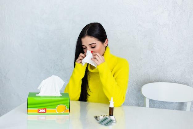 Bajo el clima. mujer joven enferma que se siente mal y se suena la nariz mientras tiene una manta sobre los hombros y se sienta en el sofá con los ojos cerrados y una mesa con pastillas frente a ella