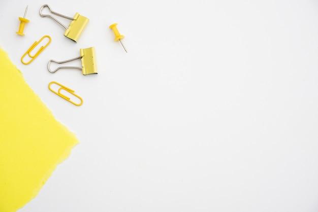 Clip amarillo y chincheta sobre fondo blanco con espacio de copia