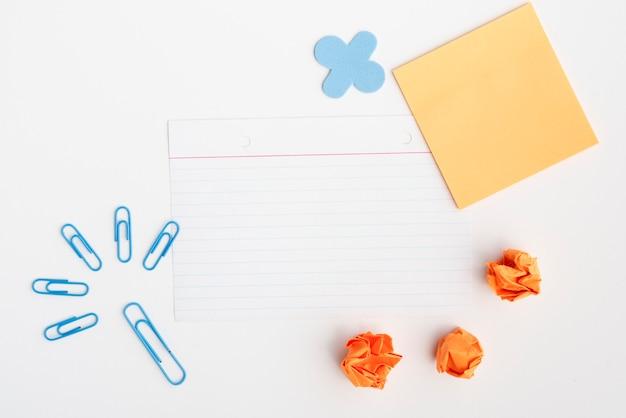 Clip azul y papel arrugado con papel vacío contra el fondo blanco.