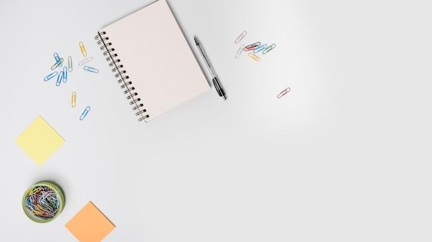 Clips de colores; libreta de espiral; bolígrafo; nota adhesiva sobre fondo blanco