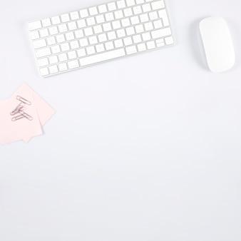 Clips de papel y notas adhesivas cerca del teclado y el mouse