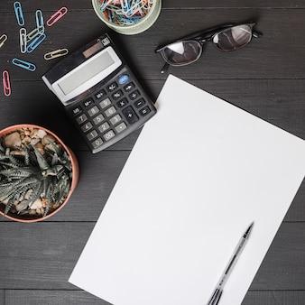 Clips de papel; calculadora; los anteojos; planta en maceta con lápiz sobre papel blanco en blanco