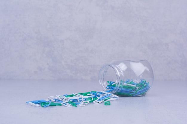 Clips de papel de colores en un frasco de vidrio contianer