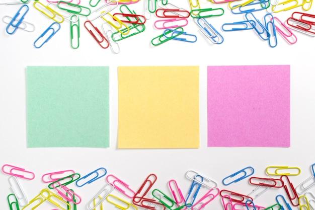 Clips de papel coloridos y 3 papeles de nota en el centro aislados en blanco.
