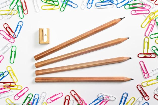 Clips de papel coloridos y lápices de madera en el centro de la composición aislados en blanco.