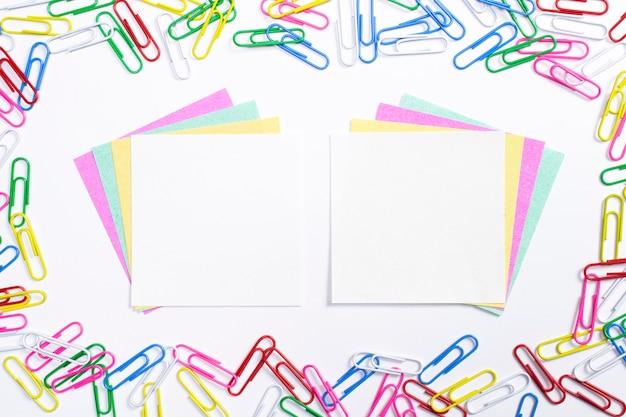 Clips de papel coloridos y papeles de nota en el centro de la composición aislado en blanco.
