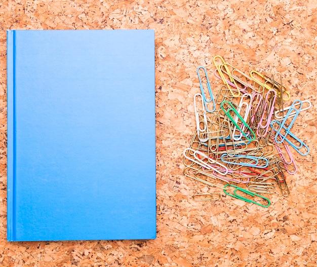 Clips de papel y cuaderno azul en tablero de corcho