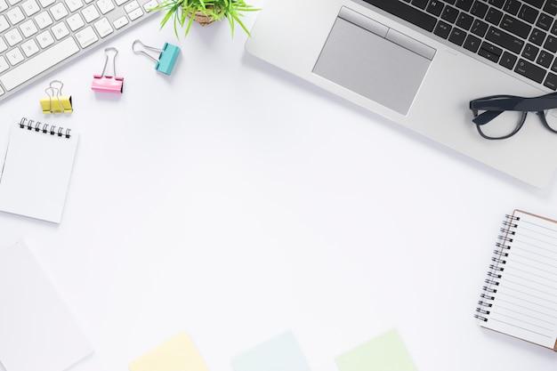Clips de papel; teclado; ordenador portátil; bloc de notas en espiral y notas adhesivas en el escritorio blanco con espacio para escribir texto