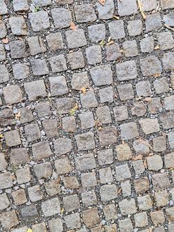 Clkoseup del pavimento de adoquines vacíos de cerca en la calle de la ciudad vieja