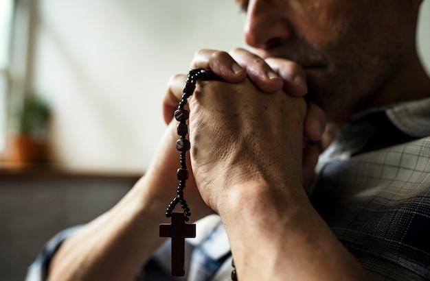 Cloesup de manos sosteniendo la cruz orando