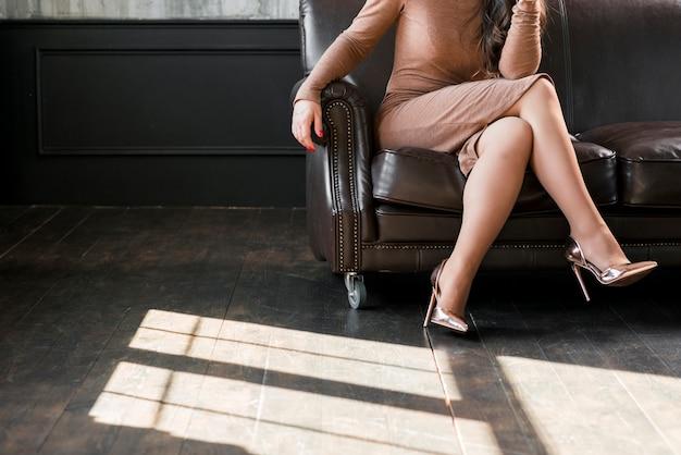 Clos-up de una mujer joven con las piernas cruzadas y usando tacones dorados sentados en un sofá