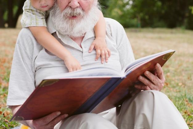 Close-up abuelo y nieto leyendo