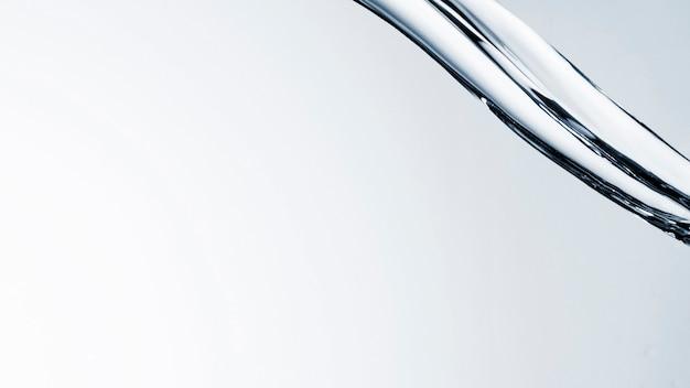 Close-up agua clara que fluye sobre fondo claro con espacio de copia