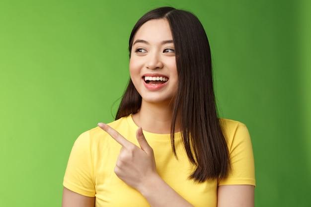 Close-up alegre amigable asiática saliente divirtiéndose, señalando a la izquierda divertido, hablando animadamente, discutiendo eventos interesantes de amigos, pararse sobre fondo verde charlando despreocupadamente entretenido.