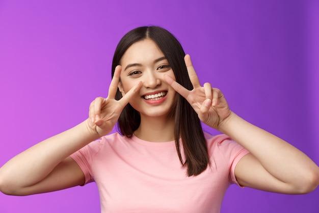 Close-up amistoso positivo saliente agradable chica asiática muestra paz, signos de victoria aprecian friendhsip mantenerse optimista, sonriendo ampliamente, tener divertidas vacaciones de verano, soporte de fondo púrpura.