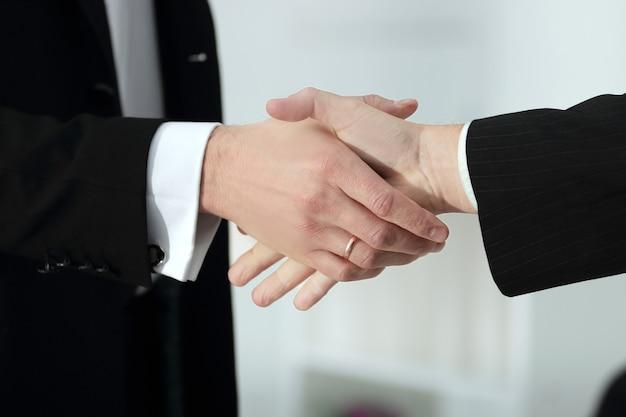 Close up.apretón de manos de socios comerciales en la oficina borrosa