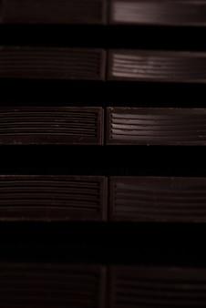 Close-up de azulejos de barra de chocolate negro en una línea.