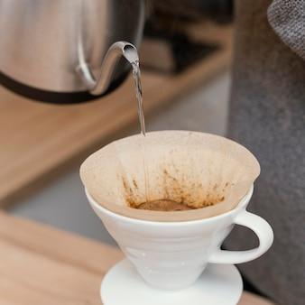 Close-up de barista macho vertiendo agua caliente sobre el filtro de café