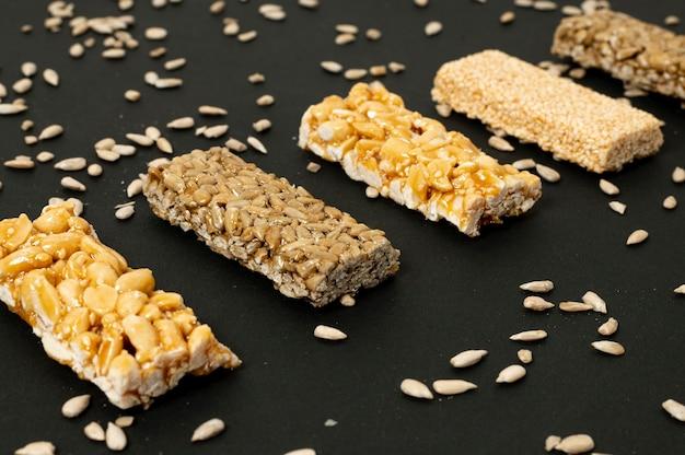 Close-up barras de cereales y semillas de girasol sobre fondo liso