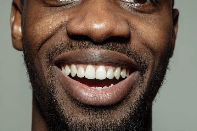 Close-up boca masculina con una gran sonrisa y dientes sanos. cosmetología, odontología y cuidados de belleza, emociones.