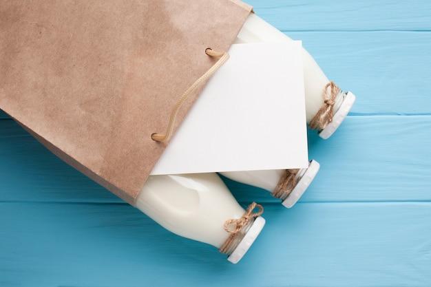 Close-up botellas de leche y tarjeta blanca