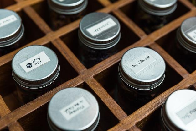 Close-up botellas de vidrio de té de flores secas con tapa de aluminio dentro de la caja de madera.