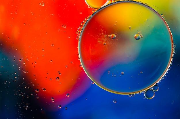 Close-up burbujas y gotas aceitosas en colorido telón de fondo acuoso