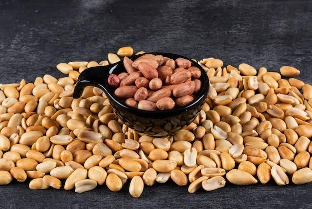 Close-up cacahuetes en un tazón rodeado de cacahuetes fritos