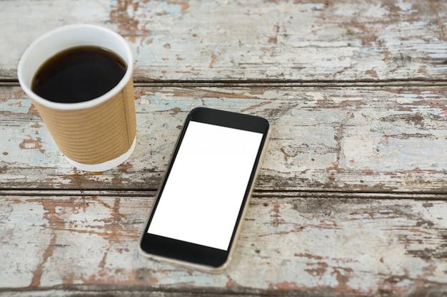 Close-up de café negro y teléfono móvil