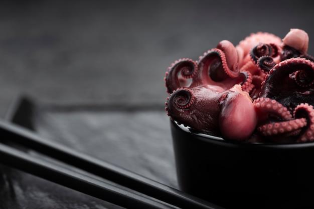 Close-up de calamares en un tazón con palillos