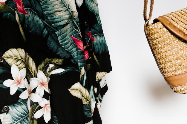 Close-up camisa tropical junto a la bolsa de paja