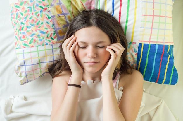 Close-up cara de adolescente en la almohada con los ojos cerrados, sosteniendo la cabeza con las manos