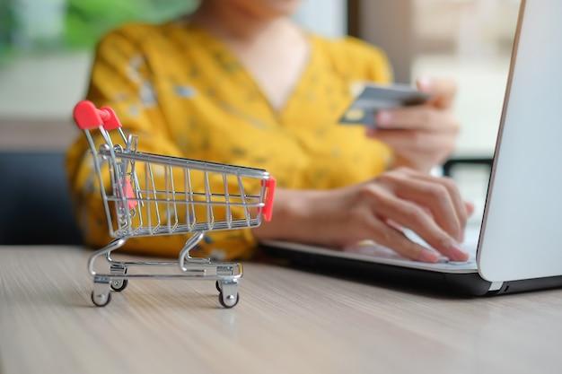 Close up carro de compras, mujer asiática con tarjeta de crédito y el uso de la computadora portátil para en línea