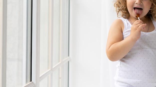 Close-up chica rubia lamiendo una piruleta