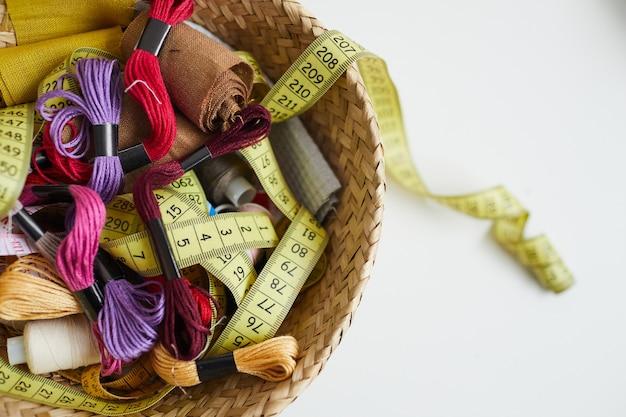 Close-up de cinta métrica de hilos de colores y otros artículos de costura en la cesta