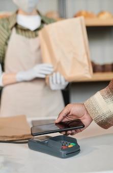 Close-up de cliente pagando la compra con teléfono móvil en la tienda