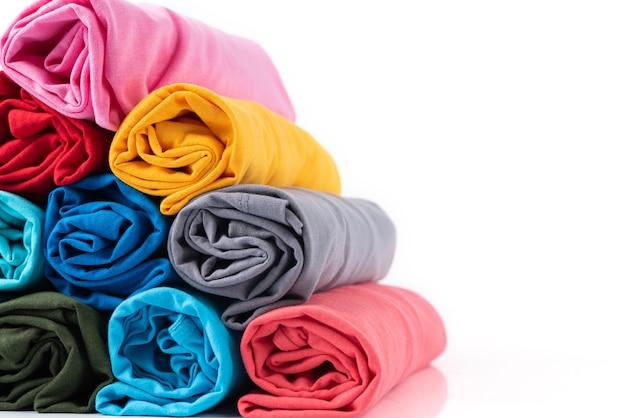 Close up colorida camiseta de algodón de rollos hecha en forma de pirámide aislada sobre fondo blanco.