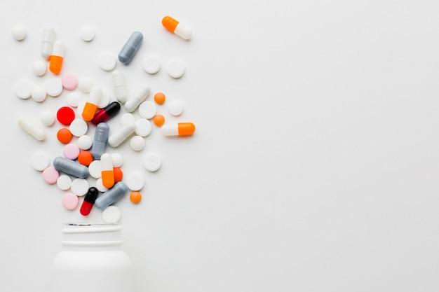 Close-up coloridas píldoras derramadas de botella de plástico