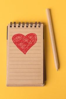 Close-up de un corazón rojo pintado en un cuaderno de papel reciclado y un bolígrafo