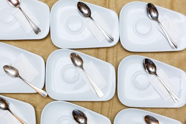 Close up dinning el tenedor, la cuchara y el cuchillo de los cubiertos con el plato en el espacio de fondo y texto blanco